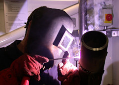 Image of a welder welding a pipe